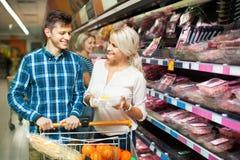 Pares de sorriso da família que escolhem a carne refrigerada Imagens de Stock Royalty Free