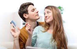 Pares de sorriso engraçados usando o cartão de crédito à loja do Internet em linha fotografia de stock