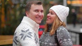 Pares de sorriso felizes na roupa morna que ri no Natal favoravelmente, homem que aponta em algum lugar Família nova engraçada al vídeos de arquivo