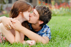 Pares de sorriso felizes novos que encontram-se ao ar livre e beijo Foto de Stock Royalty Free