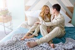 Pares de sorriso felizes que encontram-se na cama em casa imagens de stock royalty free