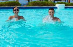 Pares de sorriso felizes que fazem a aptidão do aqua na piscina fotografia de stock