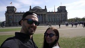 Pares de sorriso felizes que tomam o retrato de Selfie, construção de Reichstag, Berlim, Alemanha filme