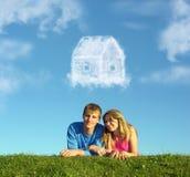 Pares de sorriso na casa da nuvem da grama e do sonho Fotos de Stock Royalty Free