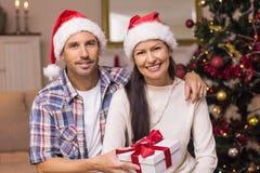 Pares de sorriso no chapéu de Santa que guarda o presente Imagens de Stock