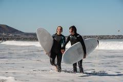 Pares de sorriso novos e felizes de surfistas nos roupas de mergulho pretos que guardam um umas outras mãos foto de stock