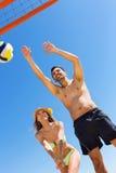 Pares de sorriso novos que jogam o voleibol fotografia de stock royalty free