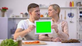Pares de sorriso novos que mostram a tabuleta com tela verde, molde culinário dos cursos video estoque