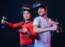 Pares de sorriso novos que têm o divertimento junto, o jogo com auriculares de VR e os controladores fotos de stock