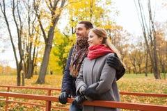 Pares de sorriso que abraçam na ponte no parque do outono Fotos de Stock