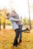 Pares de sorriso que abraçam no parque do outono Fotografia de Stock Royalty Free