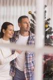 Pares de sorriso que abraçam perto da árvore de Natal Imagens de Stock