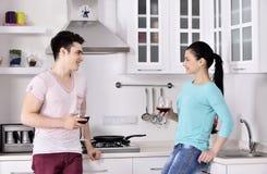 Pares de sorriso que apreciam a videira vermelha na cozinha Imagens de Stock Royalty Free