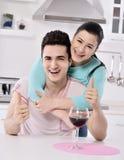 Pares de sorriso que apreciam a videira vermelha na cozinha Fotos de Stock Royalty Free