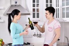 Pares de sorriso que apreciam a videira vermelha na cozinha Foto de Stock
