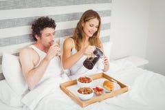 Pares de sorriso que comem o café da manhã na cama imagens de stock