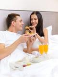 Pares de sorriso que comem o café da manhã na cama no hotel Fotos de Stock