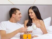 Pares de sorriso que comem o café da manhã na cama no hotel Foto de Stock Royalty Free