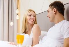 Pares de sorriso que comem o café da manhã na cama no hotel Fotografia de Stock Royalty Free