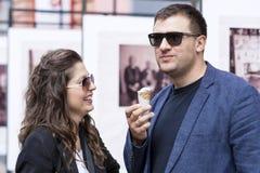 Pares de sorriso que comem o gelado na rua Imagens de Stock Royalty Free