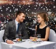 Pares de sorriso que comem o prato principal no restaurante Imagens de Stock