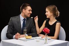 Pares de sorriso que comem a sobremesa no restaurante imagem de stock