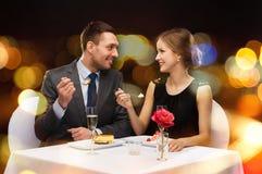Pares de sorriso que comem a sobremesa no restaurante Fotografia de Stock Royalty Free