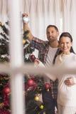 Pares de sorriso que decoram a árvore de Natal junto Fotos de Stock