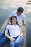 Pares de sorriso que descansam na ponte na costa do lago no por do sol Fotos de Stock Royalty Free