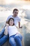 Pares de sorriso que descansam na ponte na costa do lago no por do sol Fotografia de Stock Royalty Free
