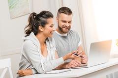 Pares de sorriso que discutem o projeto ao trabalhar em casa junto imagem de stock