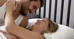 Pares de sorriso que encontram-se na cama vídeos de arquivo