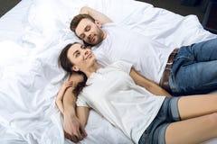 Pares de sorriso que encontram-se na cama Foto de Stock Royalty Free