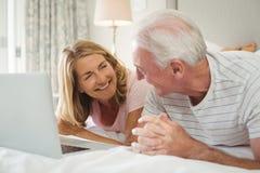 Pares de sorriso que encontram-se na cama e em usar o portátil Imagens de Stock