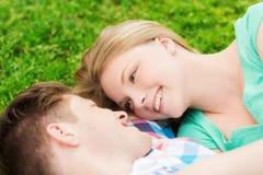 Pares de sorriso que encontram-se na grama no parque Imagens de Stock