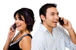 Pares de sorriso que falam em móbeis Fotos de Stock Royalty Free