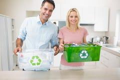 Pares de sorriso que levam reciclando recipientes na cozinha imagens de stock royalty free