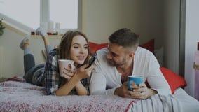 Pares de sorriso que olham a tevê ao encontrar-se na cama e que bebem o café em casa na manhã imagens de stock royalty free