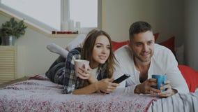 Pares de sorriso que olham a tevê ao encontrar-se na cama e que bebem o café em casa na manhã imagem de stock royalty free