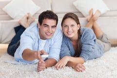 Pares de sorriso que olham a tevê ao encontrar-se em um tapete Imagens de Stock