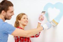 Pares de sorriso que pintam o coração pequeno na parede Fotografia de Stock Royalty Free
