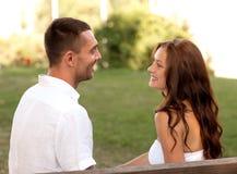 Pares de sorriso que sentam-se no banco no parque Fotografia de Stock Royalty Free
