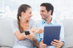 Pares de sorriso que sentam-se no sofá usando o PC da tabuleta e olhando a tevê Fotos de Stock