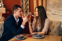 Pares de sorriso que têm o jantar e que bebem o vinho branco na data no restaurante fotos de stock royalty free