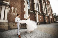 Pares de sorriso de surpresa do casamento Noiva bonita e noivo ? moda perto da igreja imagens de stock royalty free