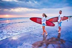 Pares de surfistas que andam na costa em Indonésia Imagem de Stock Royalty Free