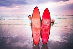 Pares de surfistas que estão na costa em Indonésia Foto de Stock Royalty Free