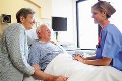 Pares de Talking To Senior de la enfermera en sitio de hospital imagen de archivo