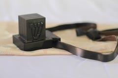 Pares de tefillin, símbolo de la gente judía, un par de A de tefillin con las correas negras, en un fondo blanco Imagen de archivo