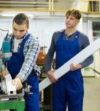 Pares de trabajadores en la fábrica Fotos de archivo